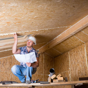 Home inspector looking at new construction of attic